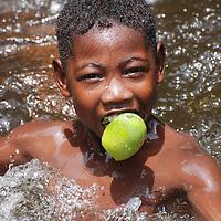 Niño del pueblo de Chuao, comiendo un mango en el río Edo. Aragua, Venezuela