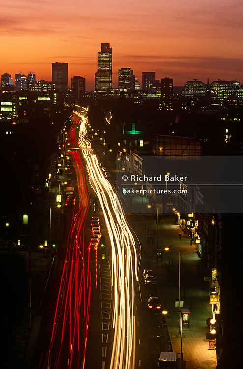 The Mile End Road leading up to the City of London with the Natwest tower on the horizon. The evening exodus is underway, the rush-hour for commuters and car drivers who head east and west along this old road to and from the City of London, through the poorer east end to the wealth and prosperity of the financial district. Light trails from the vehicles's headlights and tail lights register during a time exposure and the pink city skies to the west glow above the tall office complexes on the skyline.