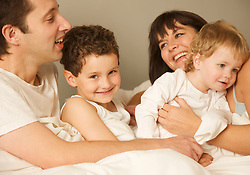 Close up of a young family in bed hugging and smiling
