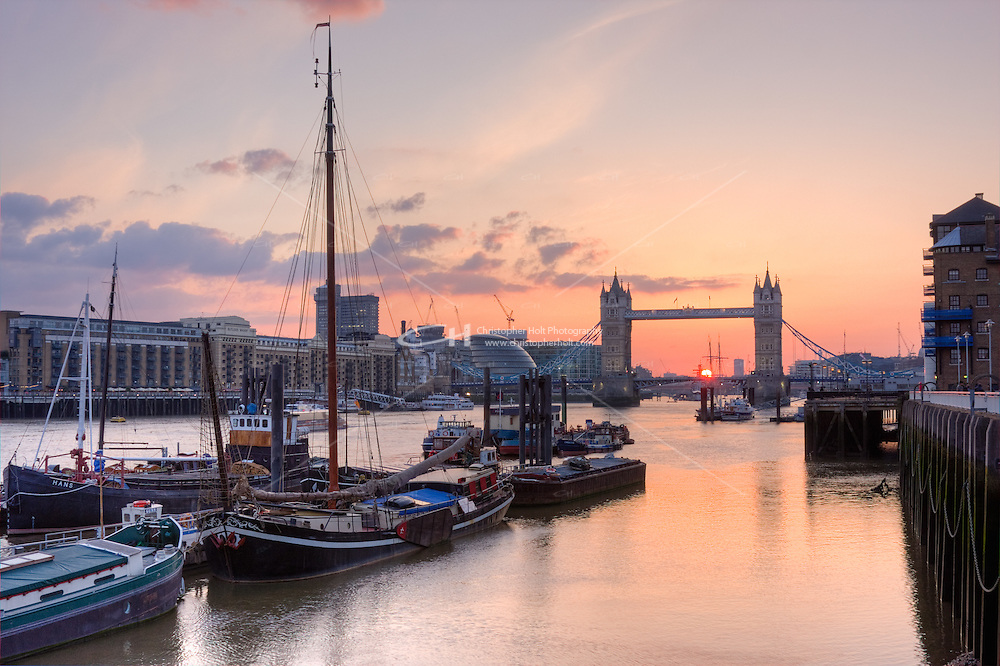 the sun sets behind tower bridge and the thames river in april 2010