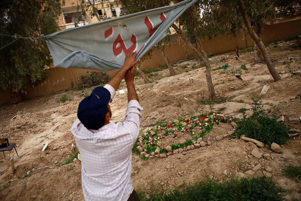 A man unfolds a banner hanging between trees on a former playground which now serves as a cemetery for victims of shelling and fighting in Deir az-Zor. Residents of eastern syrian town Deir az-Zor joined arab spring protests against the regime of Bashar al-Assad from its early beginning in March 2011. Since summer 2012 the town with few hundred thousand inhabitants is embattled between the Syrian Army and different opposing rebel groups like Free Syrian Army and Jabhat al-Nusra. Deir az-Zor is target to constant shelling by artillery, war planes and short range missiles. Almost 70 percent of the town is rebel held while government forces remain in control over some residental areas and a strategic important airport. Deir az-Zor is widely damaged and some areas almost totally destroyed by fierce and long lasting battles. All direct road connections to Deir az-Zor are cut and fighters and returning residents as well depend on one provisional supply line across the Euphrates river which is regularly targeted by government snipers.