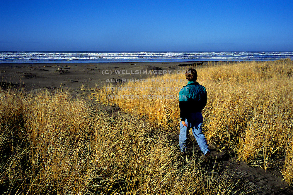 Image of a woman walking along a trail to Klipsan Beach in Long Beach, Washington, Pacific Northwest, model released