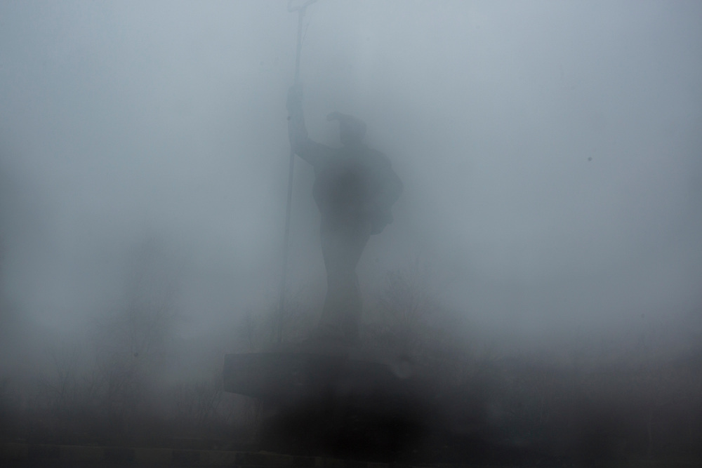 A statue of a steel worker at the northern entrance of the city is seen through a foggy window on Sunday, March 20, 2016 in Mariupol, Ukraine.
