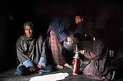 (MODEL RELEASED IMAGE). Preparing to host visitors in their home in Bhutan, Sangay pours a pot of tea into a thermos. Her half-sister Bangam holds the sieve. Meanwhile, Namgay, the family patriarch, waits patiently for a cup. Hungry Planet: What the World Eats (p. 276). The Namgay family living in the remote mountain village of Shingkhey, Bhutan, is one of the thirty families featured, with a weeks' worth of food, in the book Hungry Planet: What the World Eats.