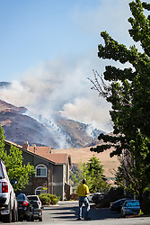 June 22, 2017 - Reno, Nevada, U.S - A spectator watches the Hunter Creek Fire from the Aviana at Tuscany apartment complex on Thursday, June 22, 2017. The fire is burning just west of downtown Reno, Nevada, on U.S. Forest Service land. According to a Truckee Meadows Fire representative, the cause of the fire is not known, but the point of origin is known. The blaze is estimated at 250 acres and is approximately 35% contained. No structures have been damaged. One firefighter suffered a minor heat-related injury. At least eight agencies are battling the fire. Washoe County park and trail access is unavailable until investigation and operations are complete. (Credit Image: © Tracy Barbutes via ZUMA Wire)