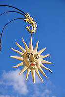 Sun sign hanging against a blue sky background at Cindis.