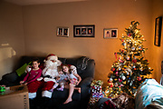 Kiara, who will be 10 tomorrow, Olivia, 4, and Destiny, who will be 9 on Thursday, sits with Santa, played by firefighter Wayne Reid, during the S.A.V.E.S Project Santa, Saturday, Dec. 22, 2018, in McSherrystown Borough. The S.A.V.E.S Project Santa donated food, toys, and clothing to 12 local families in need.