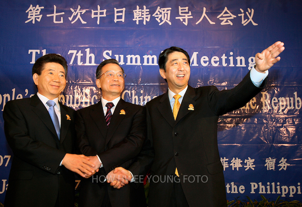 epa00902146 Japan's Prime Minister Shinzo Abe (R) gestures while shaking hands with China's Premier Wen Jiabao (C) and South Korea's President Roh Moo-Hyun as they meet for the China, Japan and South Korea summit on the sideline of the ASEAN Summit in Cebu, central Philippines on Sunday, 14 January 2007.  EPA/HOW HWEE YOUNG