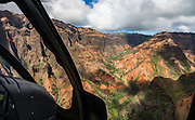 "Waimea Canyon State Park, seen via helicopter on island of Kauai, Hawaii, USA. Waimea Canyon (""the Grand Canyon of the Pacific"") slices as much as 3000 feet deep across ten miles of western Kauai. About 4 million years ago, a catastrophic collapse of the volcano that created Kauai created a fault which was gradually cut deeper by the Waimea River, fed by extreme rainfall on the island's central peak, Mount Wai'ale'ale, among the wettest places on Earth. Waimea is Hawaiian for ""reddish water,"" referring to the local orange clay. This image was stitched from multiple overlapping images."