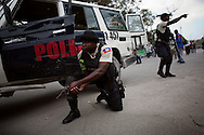 Police officers secure a street near the National Palace as Haitians stage a running protest against the government in Port-au-Prince, Haiti, February 7, 2011.