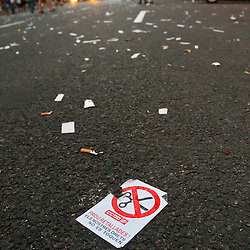 A flyer is left in a littered street after a protest against social cuts and tax increases.