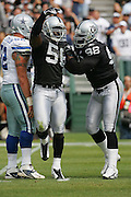 OAKLAND, CA - OCTOBER 2:  Defensive end Derrick Burgess #56 and linebacker Grant Irons #96 of the Oakland Raiders celebrates one of Burgess' two quarterback sacks against the Dallas Cowboys at McAfee Coliseum in Oakland, California on October 2, 2005. The Raiders defeated the Cowboys 19-13. ©Paul Anthony Spinelli *** Local Caption *** Derrick Burgess;Grant Irons