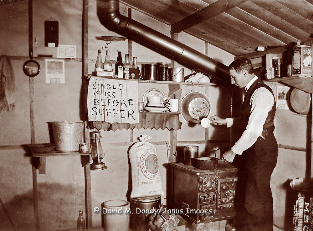 "Young man in his kitchen cooking food on a wood stove,  under a sign ""Single Bliss Before Supper""  This is the photographer's place, note developer on shelf. circa 1900"