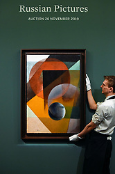 "© Licensed to London News Pictures. 22/11/2019. LONDON, UK. A technician presents ""Spherical Suprematism"", first half of the 1920s, by Ivan Kliun (Est. GBP2.5-3.5m) at the preview for the upcoming sales of Russian artworks at Sotheby's New Bond Street.  The Russian Pictures and Works of Art, Fabergé and Icons sales take place on 26 November.  Photo credit: Stephen Chung/LNP"