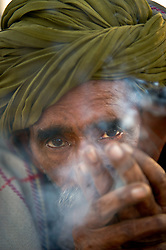 A camel trader smokes a pipe at the world's largest annual cattle fair in the desert town of Pushkar, in the Indian state of Rajasthan. Every year thousands of camel herders from the semi-nomadic Rabari tribe, who make a living rearing animals, travel for two to three weeks across 500 kilometers to set up camp in the desert dunes near Pushkar to sell their livestock. The herders sell more than 20,000 camels, horses and other animals at the annual cattle fair.