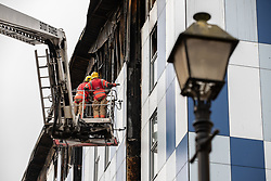 "© Licensed to London News Pictures. 16/11/2019. Bolton, UK. Firefighters work at the scene where a fire broke out overnight (15th/16th November 2019) at a block of flats known as "" The Cube "" , in Bolton Town Centre . At least two people are known to have been treated by paramedics at the scene of the six-story block , which is occupied by students of the University of Bolton . Photo credit: Joel Goodman/LNP"
