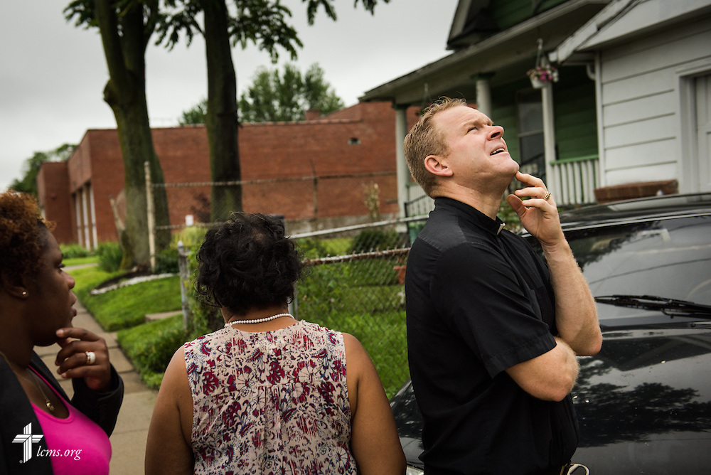 The Rev. Peter M. Burfeind, new domestic missionary and campus pastor at the University of Toledo, eye's a resident's home for repair along with community advocate Alicia Smith (far left) on Thursday, July 9, 2015, in Toledo, Ohio. LCMS Communications/Erik M. Lunsford