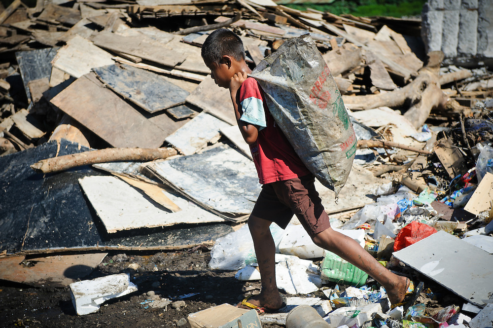 Idris, 13, returning home with a sack of plastic and metal waste for recycling at the 'Trash mountain', Makassar, Sulawesi, Indonesia.