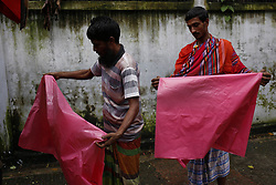 July 24, 2017 - Dhaka, Bangladesh - Bangladeshi rickshaw puller are buying plastic sheet on a rainy day to protect from rain on the street, Dhaka. (Credit Image: © Md. Mehedi Hasan via ZUMA Wire)