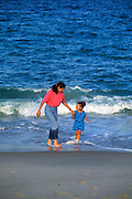 Mother and daughter having fun walking along the beach.