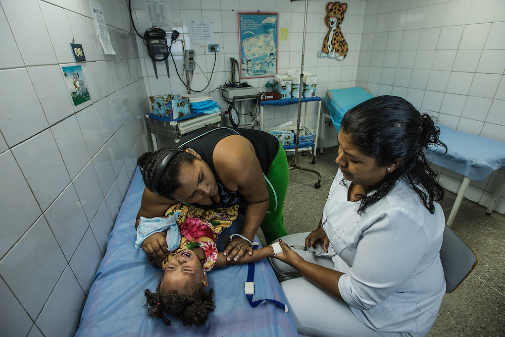 CATIA LA MAR, VENEZUELA - APRIL 12, 2016: Marbelis Reinoso holds down her daughter, who suffers from asthma,  in the pediatric emergency room of a government-run clinic in Catia La Mar. Doctors here say they regularly have to turn patients away, because they don't have the majority of medicines  or medical equipment and supplies needed to give them medical attention.  When they do accept patients, they have to work with extremely limited resources. They said they regularly run out of medicines and supplies such as IV fluids, high-blood pressure medicine, baby asprin and masks. Despite having the largest oil reserves in the world, falling oil prices and wide-spread government corruption have pushed Venezuela into an economic crisis, with the highest inflation in the world and chronic shortages of food and medical supplies.   PHOTO: Meridith Kohut for The New York Times