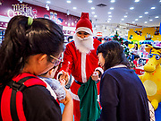 01 DECEMBER 2018 - BANGKOK, THAILAND: A Thai man in Santa Claus outfit hands out small gifts to shoppers at the Toys R Us store in Central World in Bangkok. Toys R Us closed all of their brick and mortar stores in the United States in 2018 but kept many of their overseas stores open.     PHOTO BY JACK KURTZ