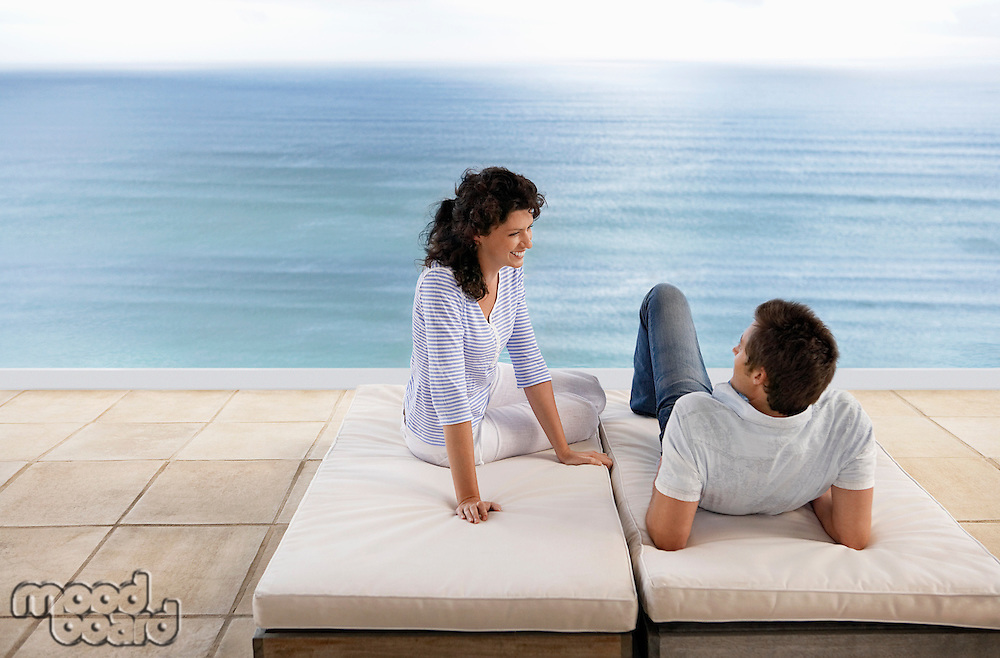 Couple relaxing on sun beds on terrace overlooking sea elevated view