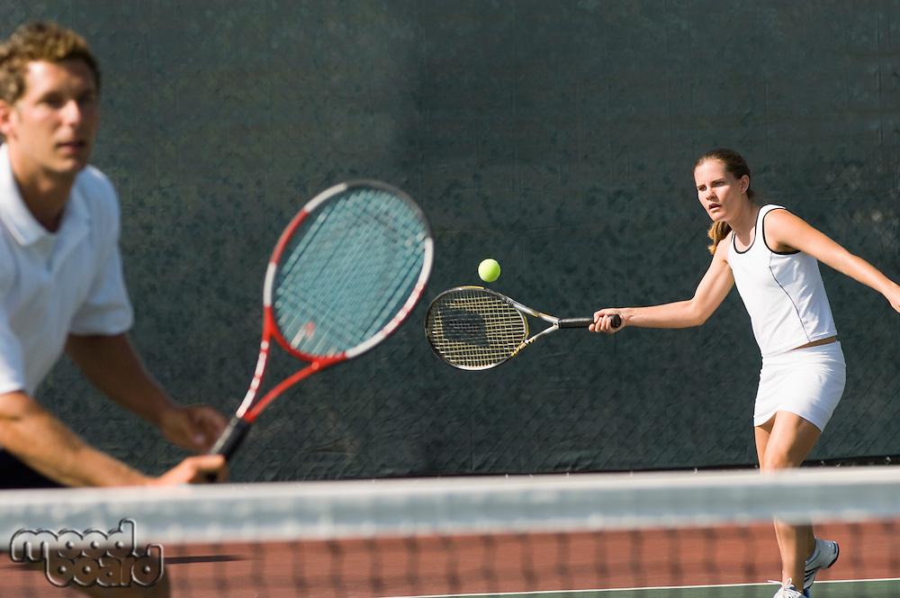 Mixed Doubles player hitting tennis ball partner standing near net