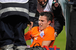 A distressed Robin Van Persie of Netherlands is treated for an injury to his right ankle during the friendly match with Italy