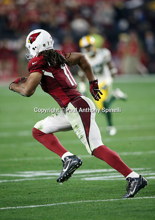 Arizona Cardinals wide receiver Larry Fitzgerald (11) catches an overtime pass and runs up field on an overtime pass good for a 75 yard gain and a first down and goal to go at the Packers 5 yard line, setting up the winning touchdown, during the NFL NFC Divisional round playoff football game against the Green Bay Packers on Saturday, Jan. 16, 2016 in Glendale, Ariz. The Cardinals won the game in overtime 26-20. (©Paul Anthony Spinelli)