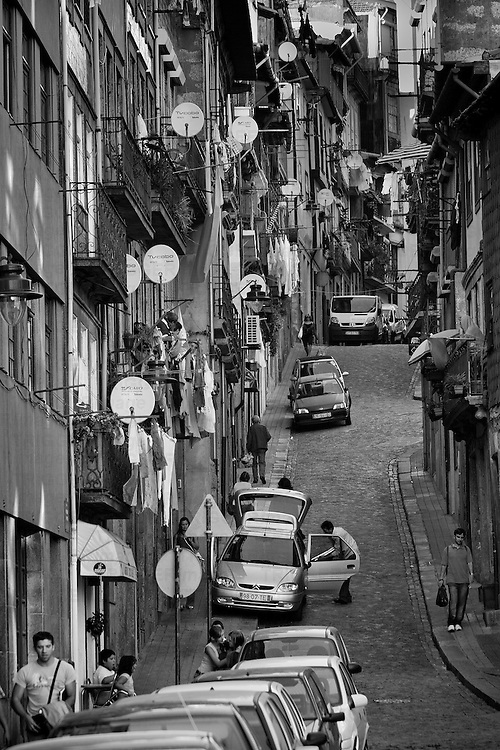 Looking along a narrow street filled with people and cars