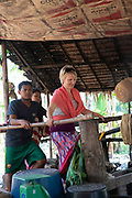 "A touris woman ""works"" with others to pound cooked rice so that it can be pressed into noodles."