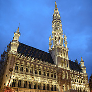 Night shot of the Town Hall (Hotel de Ville) in the Grand Place, Brussels. Originally the city's central market place, the Grand-Place is now a UNESCO World Heritage site. Ornate buildings line the square, including guildhalls, the Brussels Town Hall, and the Breadhouse, and seven cobbelstone streets feed into it.