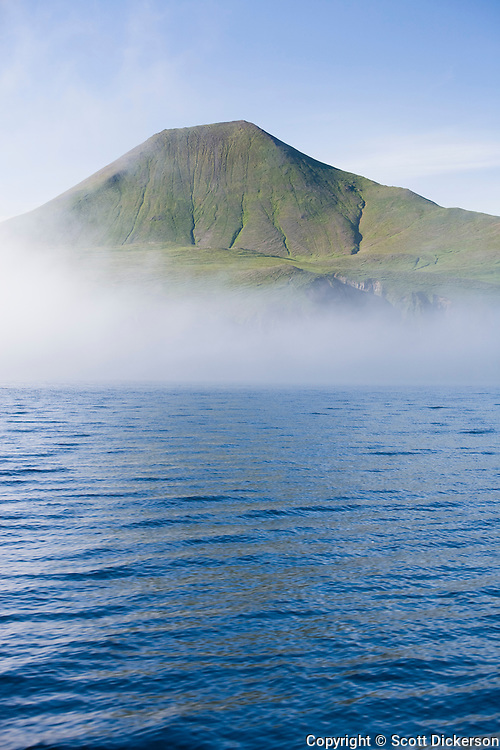 Fog spreading across the ocean partially conceals a green mountain in the Aleutian Islands, Alaska.