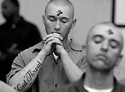 Inmate Daniel Vallee, center, prays after receiving ashes on his forehead during Ash Wednesday services at Elayn Hunt Correctional Center. Vallee and Luke Hazelton, right, attended evening services at the prison chapel with fellow inmates. ..