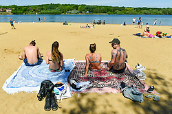 © Licensed to London News Pictures. 20/05/2020. LONDON, UK.  Two couples on the beach join members of the public taking advantage of the easing of certain coronavirus pandemic lockdown restrictions to enjoy the sunshine and warm weather at Ruislip Lido in north west London.   The forecast is for temperatures to rise to 29C, the hottest day of the year so far.  Photo credit: Stephen Chung/LNP