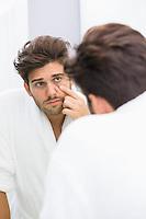Reflection of ill man examining eyes in mirror
