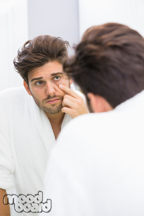 Reflection of ill man examining eyes in mirror