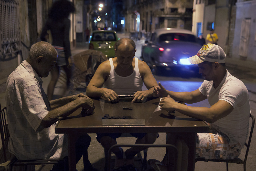 A group of me play domino at night on the streets in Centro Habana, in Havana, Cuba.