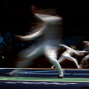 A blur of motion as Artur Akhmatkhuzin, Russia, (left) competes with Jianfei Ma, China, (foreground) and Alexey Cheremisinov, Russia, (left) competes with Alexander Massialas, USA (background) in the Men's Foil Individual event during the Fencing competition at ExCel South Hall during the London 2012 Olympic games. London, UK. 31st July 2012. Photo Tim Clayton