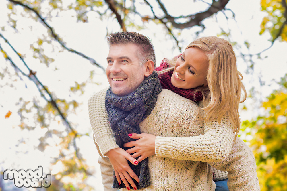Portrait of mature attractive man giving his wife a piggy ride back in park