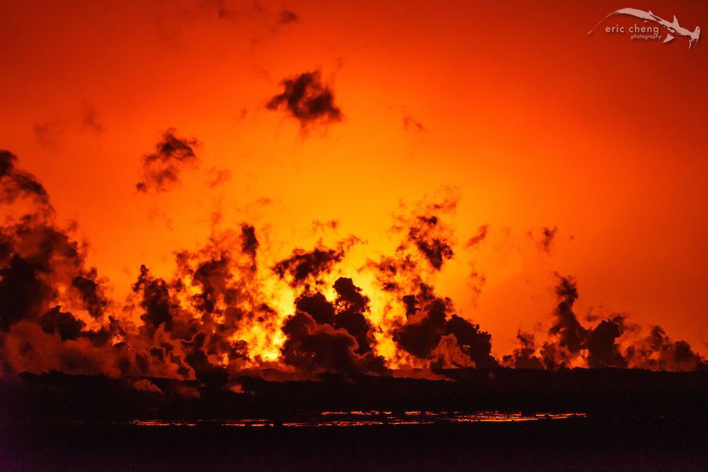 Steam rises from the lava flow at the Holuhraun eruption. The glow of the eruption lights up the sky in the background. Bardarbunga volcanic system, Iceland.