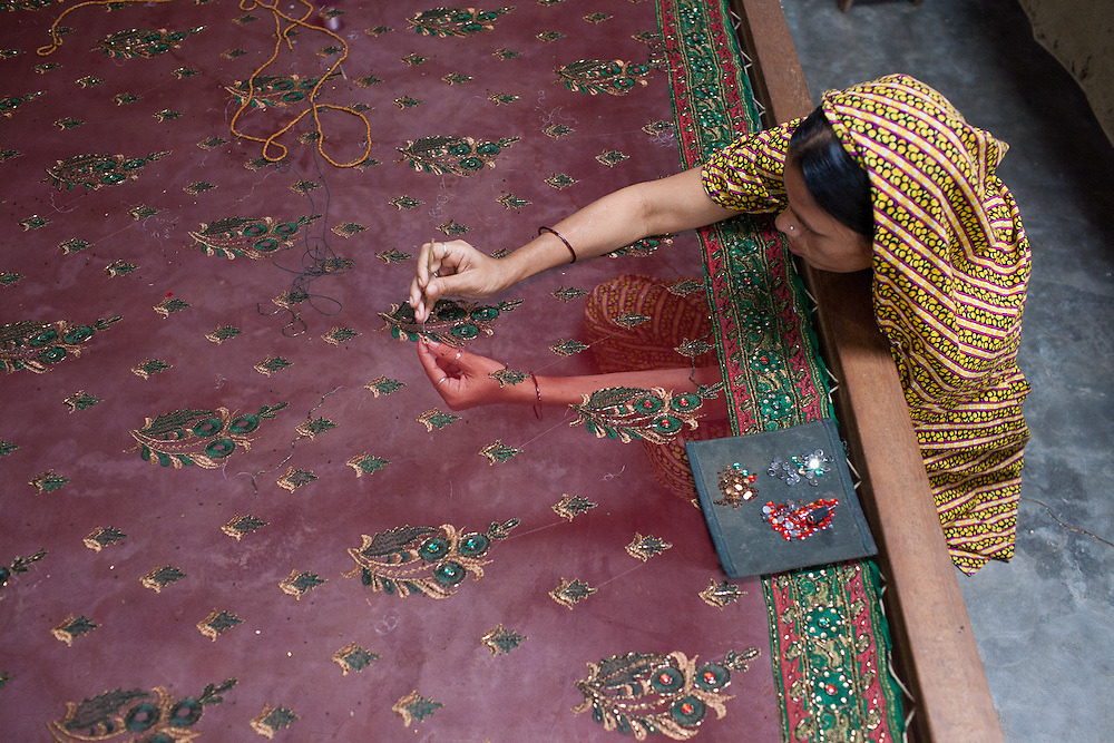 A woman sews detail into a traditional Jamdani sari in Mirpur Benarashi Palli, Dhaka, Bangladesh, a poor Bengali neighborhood.