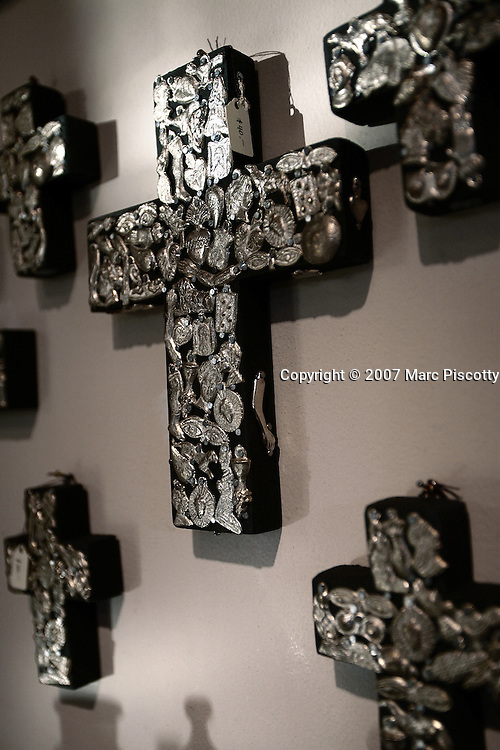SHOT 12/26/2007 - Milagros adorn a cross for sale at Saints & Martyrs in Old Town Albuquerque. The area is a historic district in Albuquerque, New Mexico, dating back to the founding of the city by the Spanish in 1706. Today it is a popular shopping and tourist destination. Old Town comprises about ten blocks of historic adobe buildings grouped around a central plaza (a common feature of Spanish colonial towns). Many of the buildings in Old Town are houses that have been converted into restaurants and small art and souvenir shops. Albuquerque is the largest city in the state of New Mexico, United States. It is the county seat of Bernalillo County and is situated in the central part of the state, straddling the Rio Grande. Milagros (also known as ex-votos or dijes) are religious folk charms that are traditionally used for healing purposes and as votive offerings in Mexico, the southern United States, other areas of Latin America, as well as parts of the Iberian peninsula. They are frequently attached onto altars, shrines, and sacred objects found in places of worship, and they are often purchased in churches, cathedrals or from street vendors. Milagros come in a variety of shapes and dimensions and are fabricated from many different materials, depending on local customs. For example, they might be nearly flat or fully three dimensional; and they can be constructed from gold, silver, tin, lead, wood, bone, or wax. In Spanish, the word milagro literally means miracle or surprise..(Photo by Marc Piscotty/ © 2007)