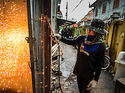 28 SEPTEMBER 2015 - BANGKOK, THAILAND:  A demolition worker uses a cutting torch to take about a metal gate in a home at Wat Kalayanamit. Fifty-four homes around Wat Kalayanamit, a historic Buddhist temple on the Chao Phraya River in the Thonburi section of Bangkok, are being razed and the residents evicted to make way for new development at the temple. The abbot of the temple said he was evicting the residents, who have lived on the temple grounds for generations, because their homes are unsafe and because he wants to improve the temple grounds. The evictions are a part of a Bangkok trend, especially along the Chao Phraya River and BTS light rail lines. Low income people are being evicted from their long time homes to make way for urban renewal.   PHOTO BY JACK KURTZ