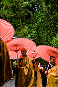 Monks with red laquered umbrellas.