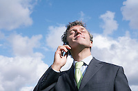 Business man talking on mobile phone smiling sky in background