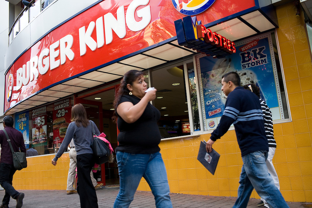 """People walk in front of a Burger King advertising an """"Extra Thick Mega Angus Burger"""" in Mexico City."""