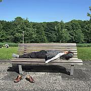 Nederland Rotterdam 24-05-2009 20090524 Foto: David Rozing .                                                                                    .Man ligt te zonnen op bankje, schoenen uit, genieten van zomerweer Kralingse plas                             .Man enjoying sunny weather          .Holland, The Netherlands, dutch, Pays Bas, Europe deelgemeente Kralingen Crosswijk  ..Foto: David Rozing