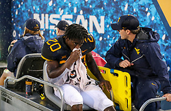 Sep 8, 2018; Morgantown, WV, USA; West Virginia Mountaineers running back Alec Sinkfield (20) leaves the field after an injury during the second quarter against the Youngstown State Penguins at Mountaineer Field at Milan Puskar Stadium. Mandatory Credit: Ben Queen-USA TODAY Sports